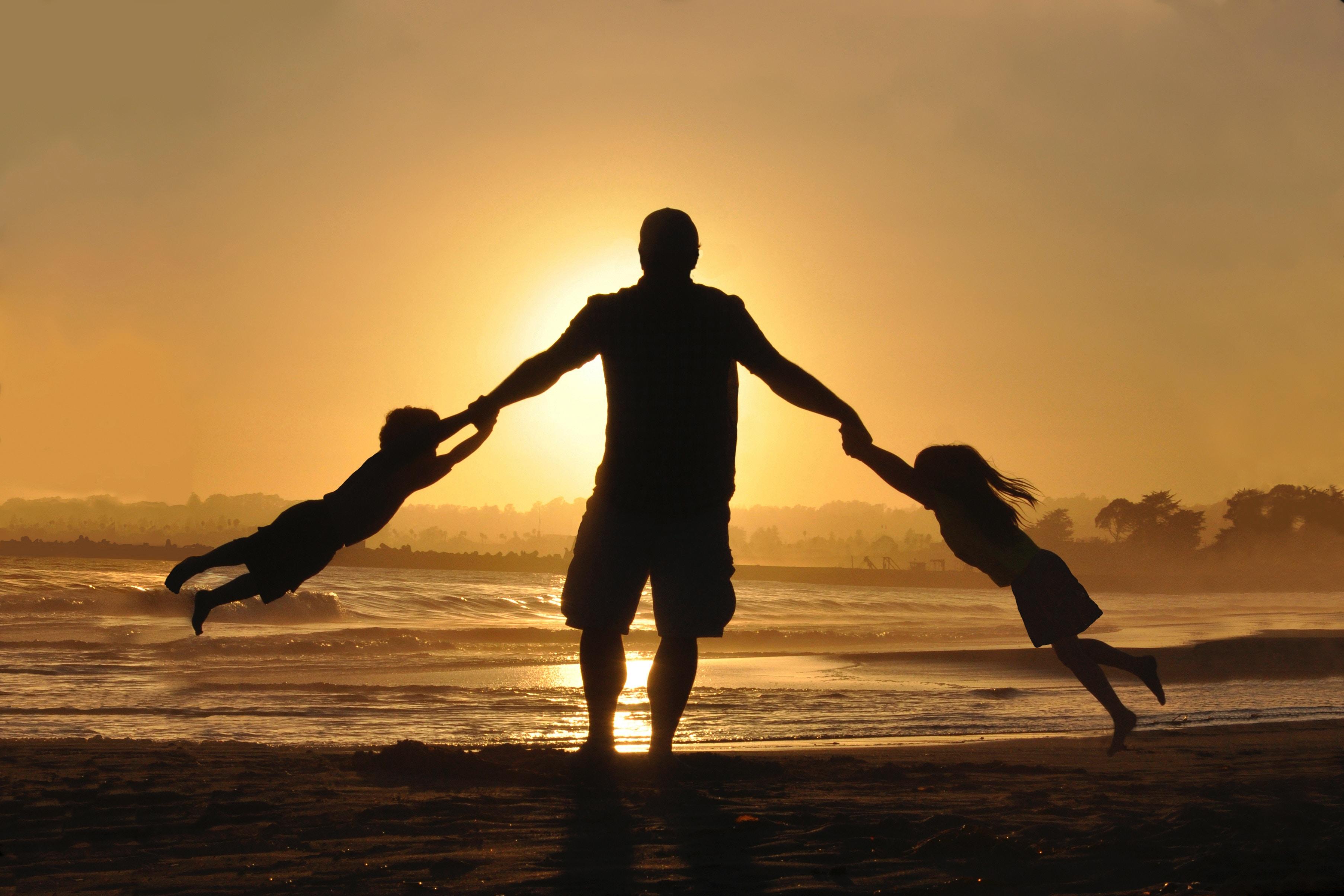 Oče z dvema otrokoma na plaži ob sončnem zahodu