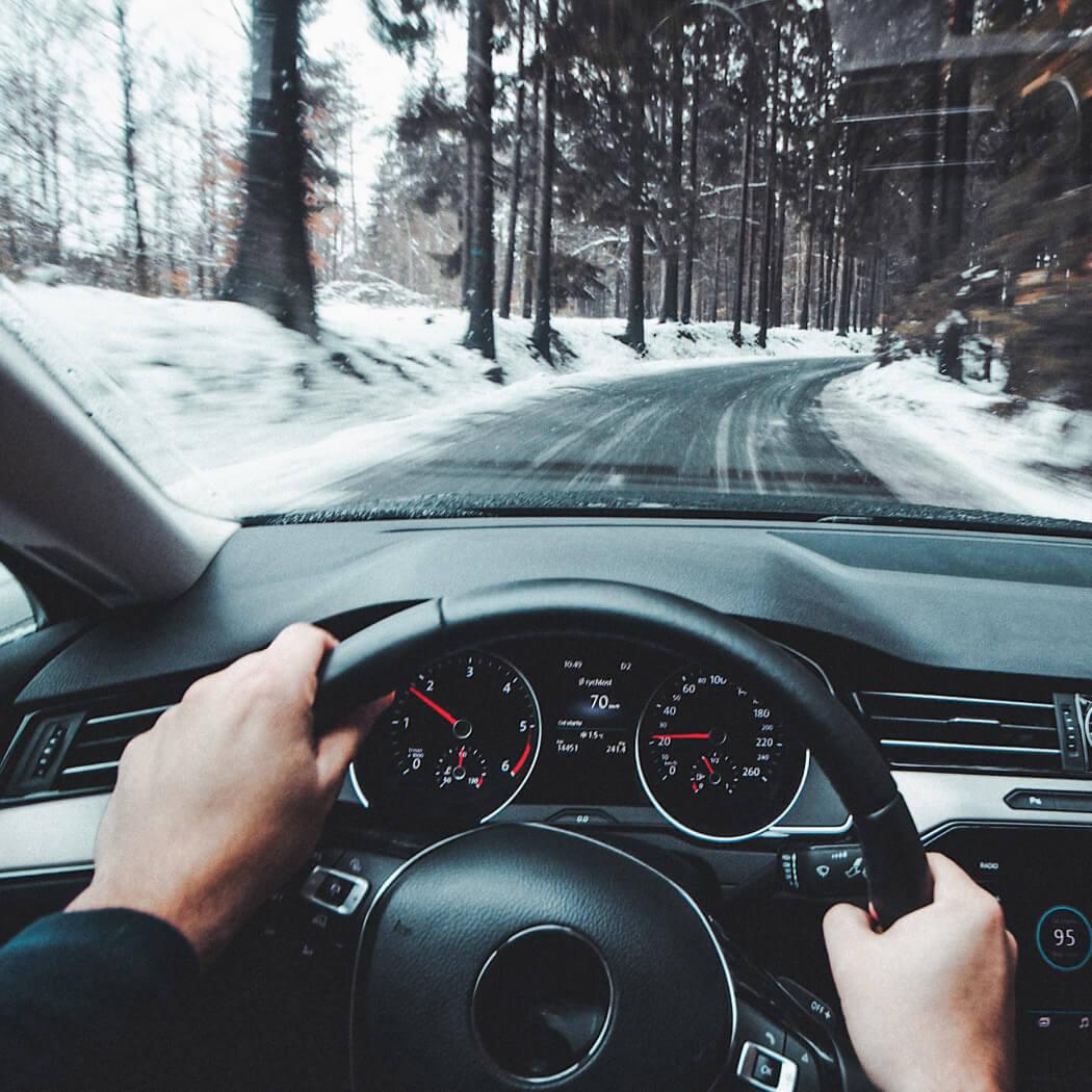 notranjost avtomobila za volanom in zasnežena cesta
