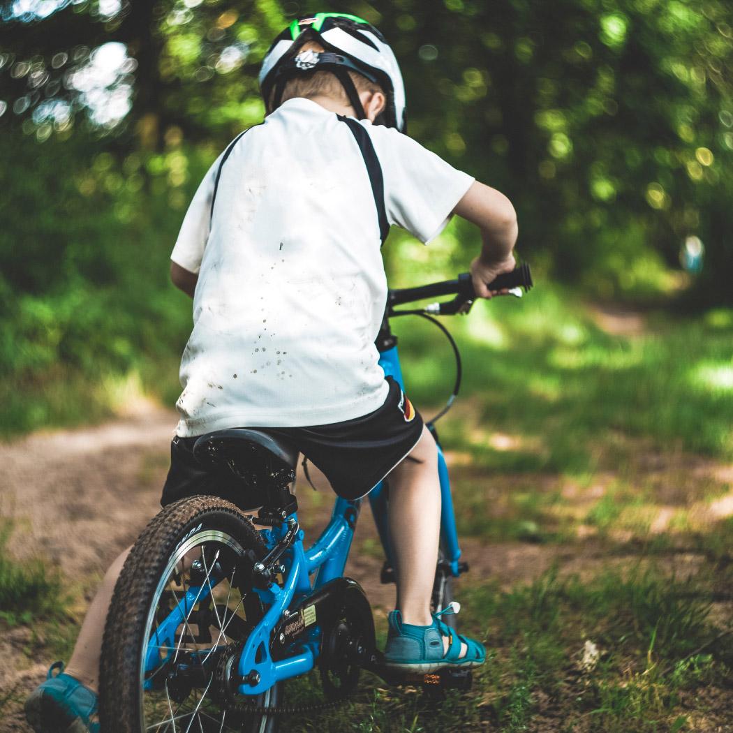 otrok na kolesu z belo čelado